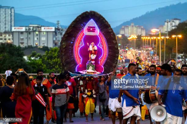 Hindu devotees carries a kavadi as he perform a prayer at Batu Caves temple during Thaipusam festivals on January 21 2019 outside Kuala Lumpur...