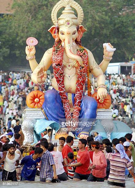 Hindu devotees carry a big clay idol of the elephant headed Hindu God Lord Ganesh into the water for immersion at the Chowpatty beach in Bombay 27...