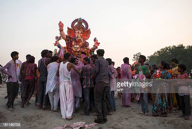 Hindu devotees carry an idol of elephantheaded Hindu god Ganesha for immersion in the Yamuna river at the conclusion of the Ganesha festival in New...