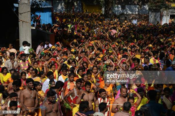 Hindu devotees carry milk pots with their cheeks pierced with a metal rod as they take part in a procession to mark the Hindu festival 'Maha...