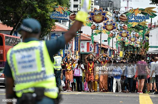 Hindu devotees carry offerings of milk during a procession to celebrate the annual Thaipusam festival in the Little India district of Singapore on...
