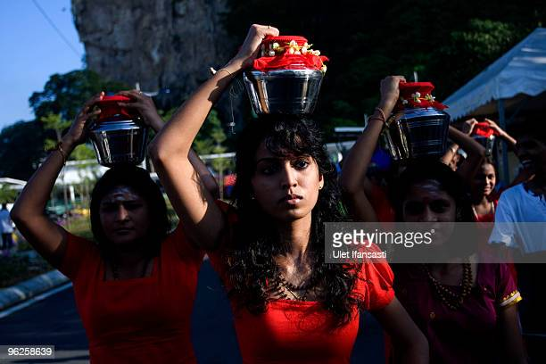 Hindu devotees carry pots of milk on their heads as they make their way towards the Batu Caves temple during the Thaipusam Hindu festival on January...