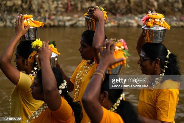 Hindu devotees carry pots of milk on their heads before their pilgrimage to the sacred Batu Caves temple during the Thaipusam festival on January 18...