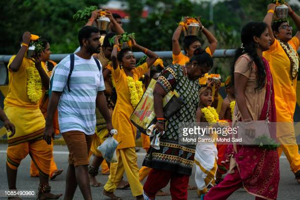 Hindu devotees carry pots with milk on their heads for their pilgrimage to the sacred Batu Caves temple during Thaipusam festivals on January 20 2019...