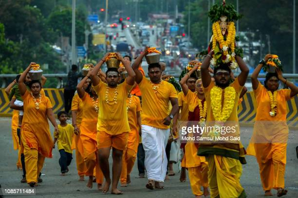 Hindu devotees carry pots with milk on their heads for their pilgrimage to the sacred Batu Caves temple during Thaipusam festivals on January 21 2019...