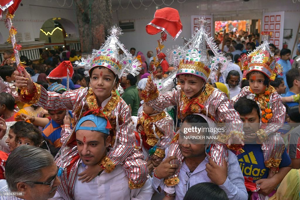 Hindu devotees carry their children dressed to honour the Hindu monkeygod Hanuman as they pay a visit to Bara Hanuman Temple of the Durgiana Temple...