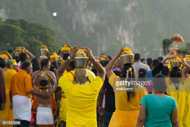 hindu devotees carrying a milk pot in their head during thaipusam festival - shaifulzamri stock pictures, royalty-free photos & images