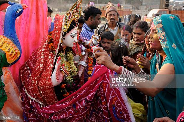 Hindu devotees celebrate after immerse the idol of Goddess Saraswati into the Yamuna river during the Vasant Panchami festival or Basant Panchami on...
