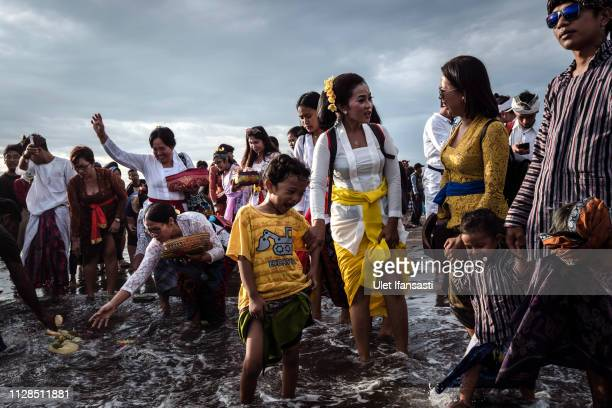 Hindu devotees clean them self with sea water as they pray during the Melasti ritual ceremony at Parangkusumo beach on March 3 2019 in Yogyakarta...