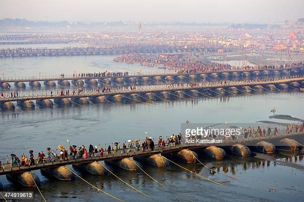 Hindu devotees cross pontoon bridges to the Sangam the confluence of the Yamuna Ganges and mythical Saraswati rivers during the Maha Kumbh Mela
