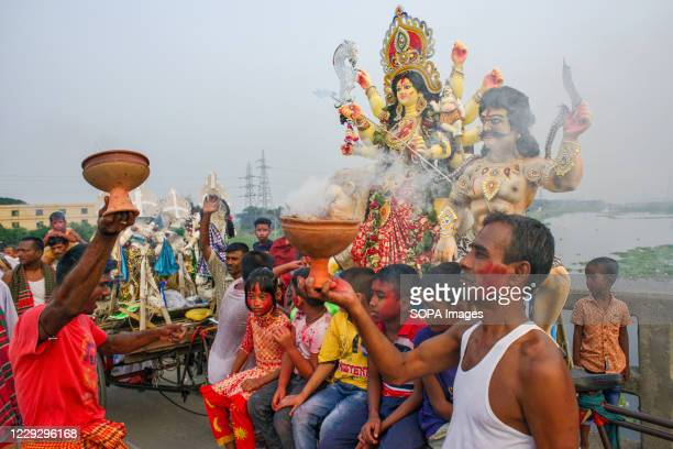 Hindu devotees dancing while taking goddess Durga to immersion at the Buriganga River after celebrating the final day of the festivity. Durga Puja,...