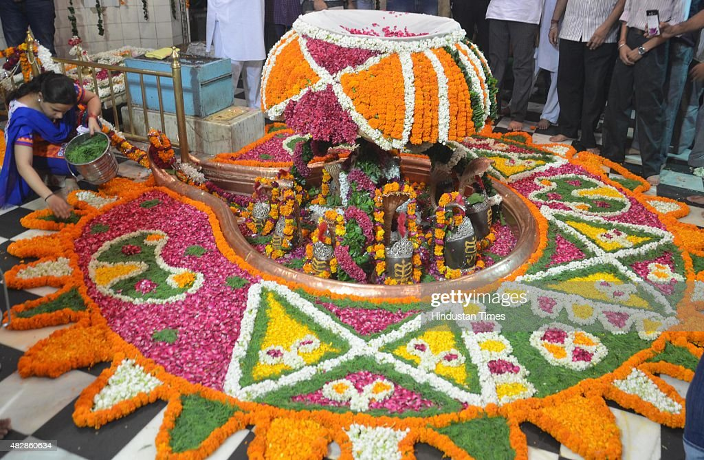 Hindu devotees decorating the Lord Shiva lingam with flowers at the historic Veer Bhan Temple on the first Monday of the Hindu holy month of Shravan..