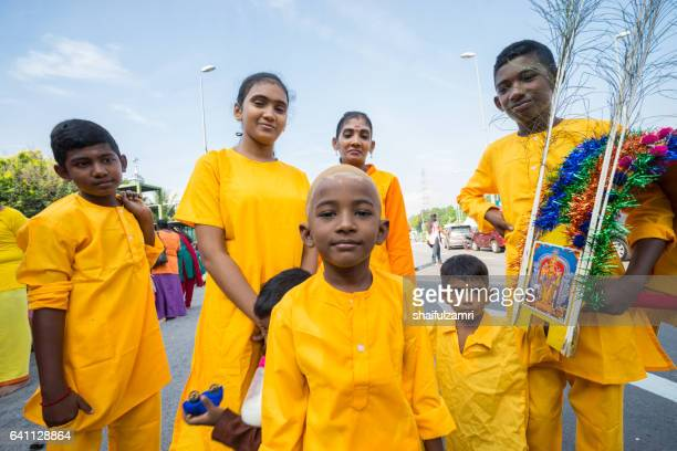 hindu devotees dress in yellow or orange colour during thaipusam festival in batu caves temple - shaifulzamri stock pictures, royalty-free photos & images