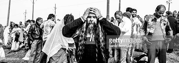 Hindu devotees dress themselves after having bathed on the banks of Sangam on January 13 2013 in Allahabad India The Maha Kumbh Mela believed to be...