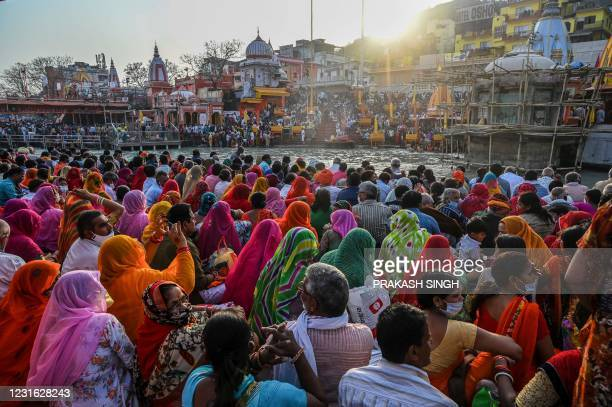 Hindu devotees gather for evening prayers after taking a holy dip in the waters of the River Ganges on the eve of Shahi Snan on Maha Shivratri...