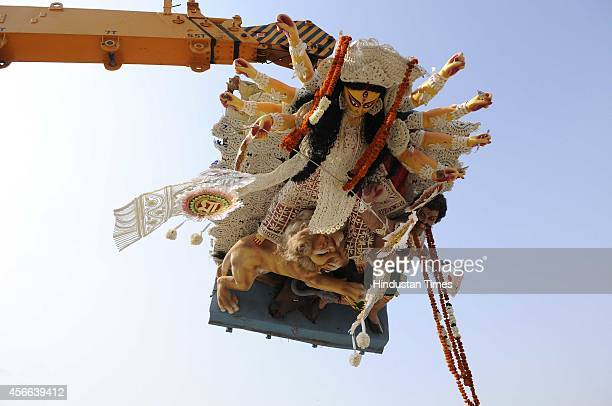 Hindu devotees immerse the idol of Goddess Durga on the final day of the Dussehra festival on October 4 2014 in Noida India Durga Puja commemorates...
