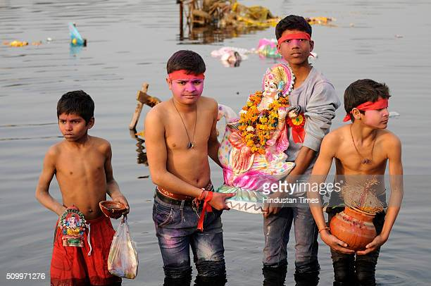 Hindu devotees immerse the idol of Goddess Saraswati into the Yamuna river during the Vasant Panchami festival or Basant Panchami on February 13 2016...
