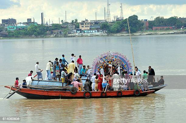 Hindu devotees in boats immerse a statue of the Hindu goddess Durga into the Ganges river during the immersion ceremony of Durga Puja in the eastern...