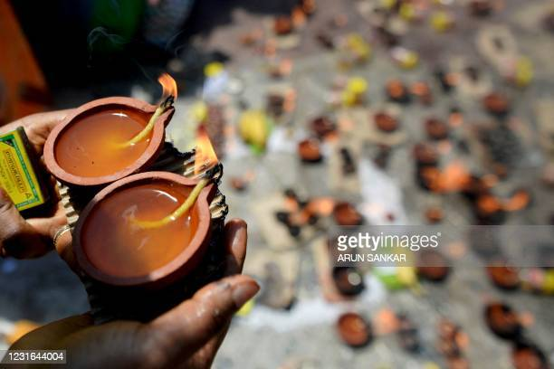 Hindu devotees light oil lamps as they perform rituals on the occasion of the Maha Shivaratri festival at a temple in Chennai on March 11, 2021.