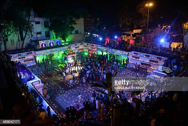 Hindu devotees light oil lamps at a temple for the Hindu God Shiva during the Karthigai Deepam in Bangalore on December 2 2013 Karthigai Deepam is a...