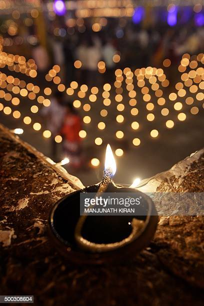 Hindu devotees light oil lamps at a temple for the Hindu God Shiva during the celebration of the Tamil Hindu festival of Karthigai Deepam in...