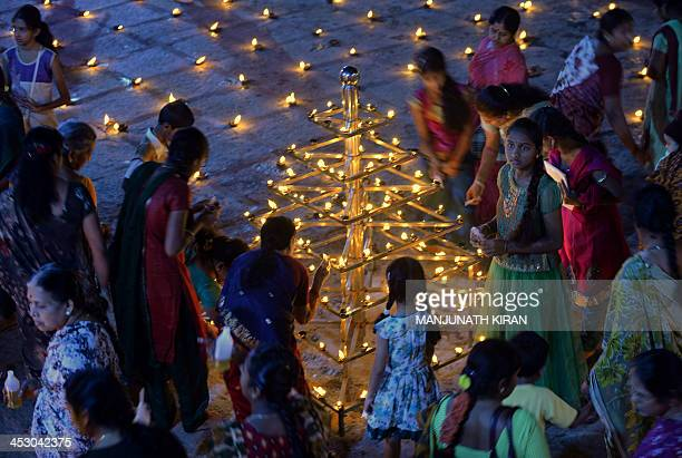Hindu devotees light oil wick lamps at a temple for the Hindu God Shiva during the Karthigai Deepam in Bangalore on December 2 2013 Karthigai Deepam...