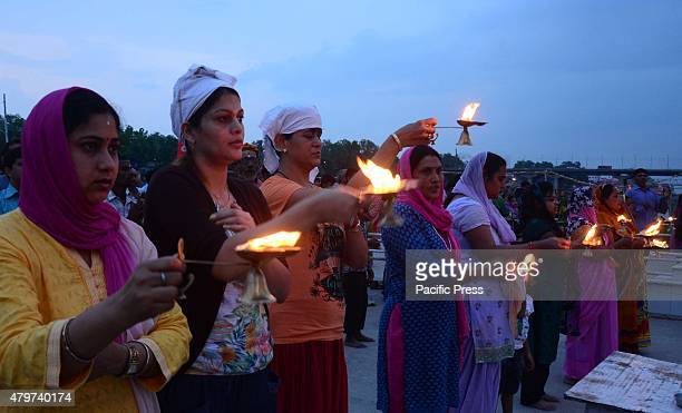 Hindu devotees offer evening prayer at bank of Sangam, confluence of River Ganga Yamuna and Mythological Saraswati during Purshottam month in...