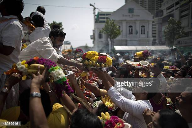 Hindu devotees offer food as they pray in front of Lord Muruga's silver chariot during the Thaipusam Hindu festival in Penang northern Malaysia...