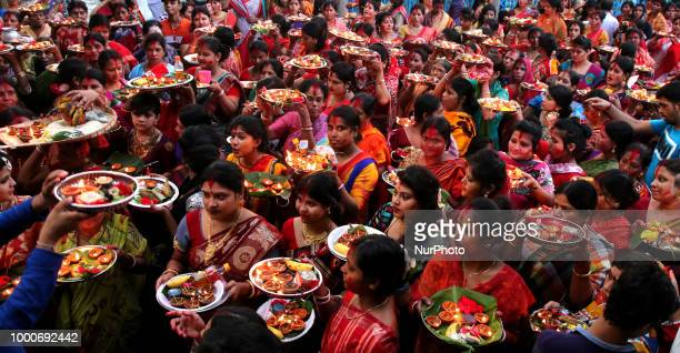 Hindu devotees offer prayer hold lamps as they attend a ritual named Bipodnashini Puja that Puja against evil and danger at street of Dhaka in Dhaka...