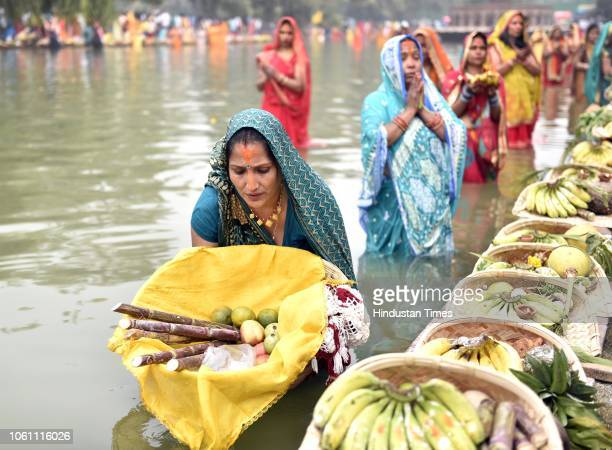 Hindu devotees offer prayers during the Chhath festival while standing in a water body near India Gate on November 13 2018 in New Delhi India...