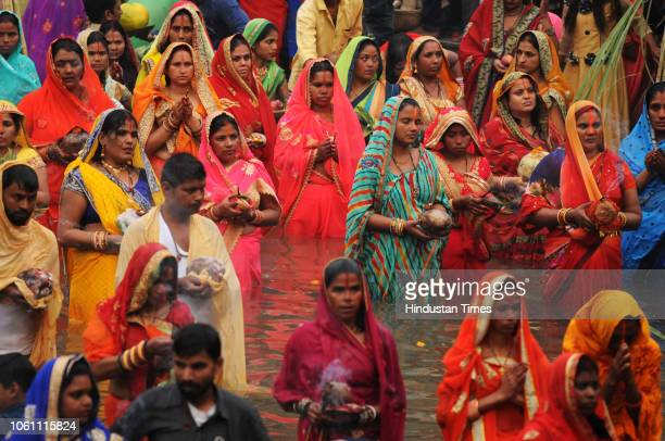 Hindu devotees offer prayers on the occasion of Chhath Puja at Sheetla Mata temple pond on November 13 2018 in Gurugram India Thousands of devotees...