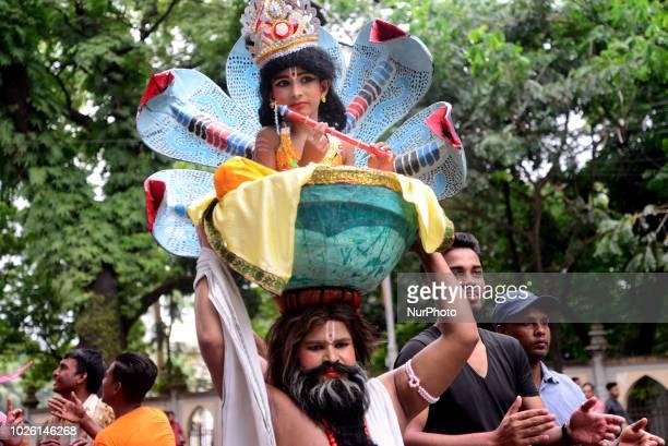 Hindu devotees parade as they take part in the celebrations of Janmashtami a festival marking the birth of Hindu deity Krishna in Dhaka Bangladesh on...