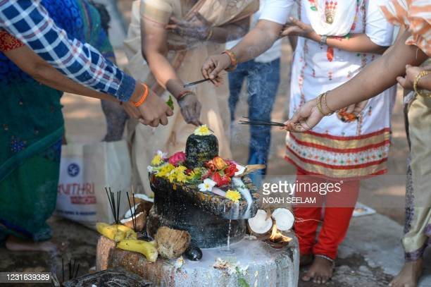 Hindu devotees perform rituals to a Shiva Lingam, a stone sculpture representing the phallus of the Hindu deity Shiva, on the occasion of Maha...