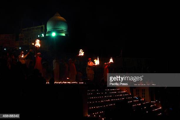 Hindu devotees perform 'Yamuna aarti' at the bank of river Yamuna decorated with thousands of earthen lamps to celebrate annual festival 'Kartik...