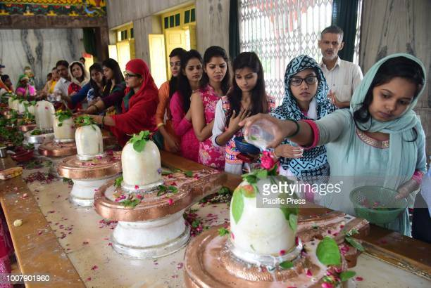 Hindu devotees performing Abhishek to Lord Shiva as they offer prayer at a temple on the 1st monday of Shrawan Month