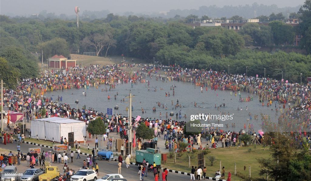 Hindu devotees performing rituals to the God Sun during sunset to mark Chhath Puja festival at Sec 42 Lake on October 26 2017 in Chandigarh India...