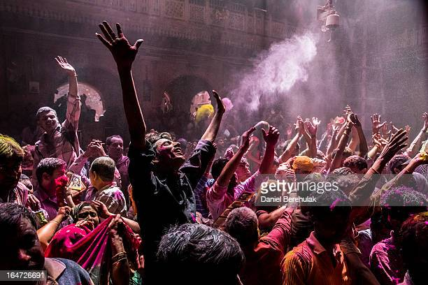Hindu devotees play with colour during Holi celebrations at the Banke Bihari temple on March 27 2013 in Vrindavan India The tradition of playing with...