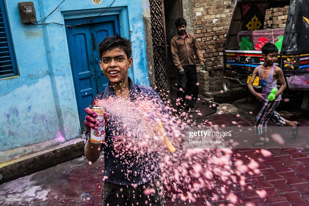 Hindu devotees play with colour during Holi celebrations in the back streets close to the Banke Bihari temple on March 27, 2013 in Vrindavan, India. The tradition of playing with colours on Holi draws its roots from a legend of Radha and the Hindu God Krishna. It is believed that young Krishna was jealous of Radha's fair complexion since he himself was very dark. After questioning his mother Yashoda on the darkness of his complexion, Yashoda, teasingly asked him to colour Radha's face in which ever colour he wanted. In a mischievous mood, Krishna applied colour on Radha's face. The tradition of applying color on one's beloved is being religiously followed till date.