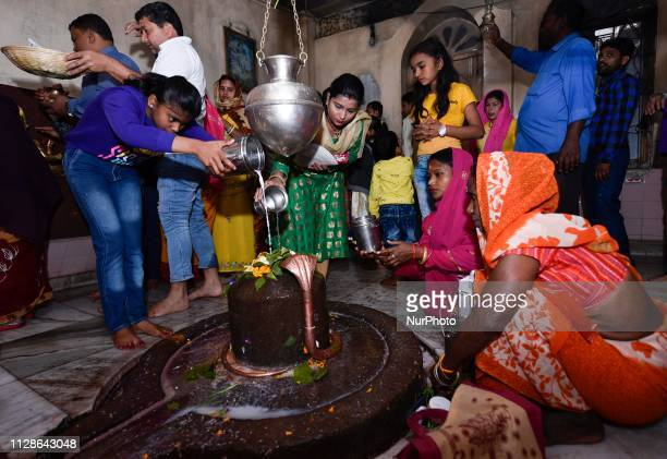 """Hindu devotees pour water and milk over a Lingam, representing Lord Shiva, at a temple on the ocassion of the """"Maha Shivratri"""" festival in..."""