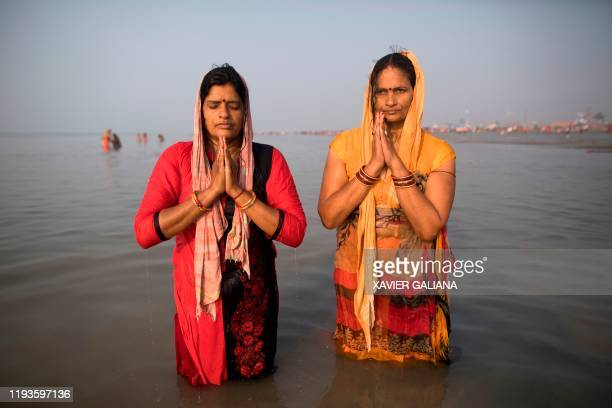 Hindu devotees pray after taking a holy dip in the Bay of Bengal during the Gangasagar Mela, at Sagar Island, some 150 kilometres south of Kolkata on...