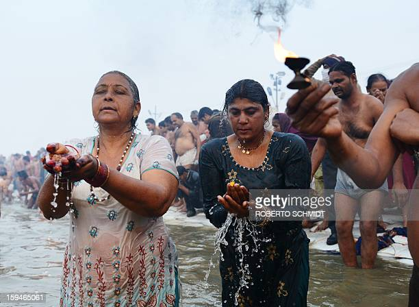 Hindu devotees pray in the waters of the Sangham or the confluence of the the Yamuna and Ganges rivers during the Kumbh Mela in Allahabad on January...