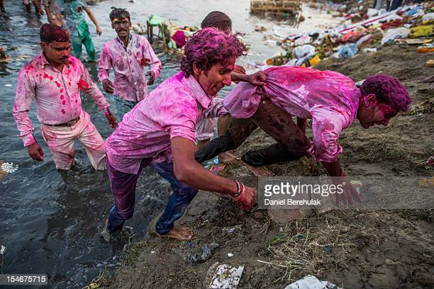 Hindu devotees pull themselves from the Yamuna river after having immersed an idol of Goddess Durga into the Yamuna river on the last day of the...