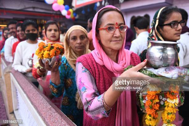 Hindu devotees queue to perform rituals to a Shiva Lingam, a stone sculpture representing the phallus of the Hindu deity Shiva, on the occasion of...
