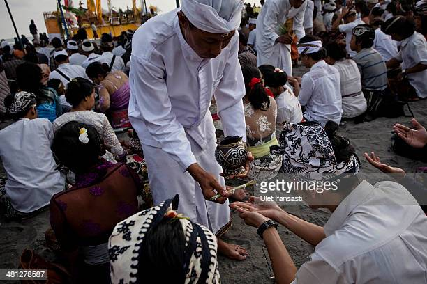 Hindu devotees receive holy water as they pray during the Melasti ritual ceremony at Parangkusumo beach on March 28 2014 in Yogyakarta IndonesiaThe...