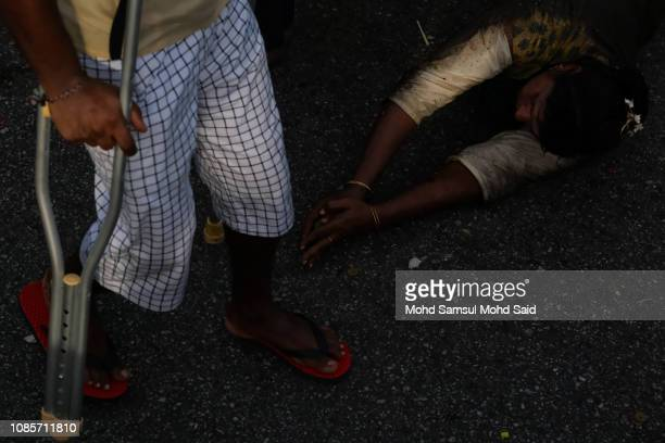 Hindu devotees roll her body over the highway as she pilgrimage to the sacred Batu Caves temple during Thaipusam festivals on January 21 2019 outside...