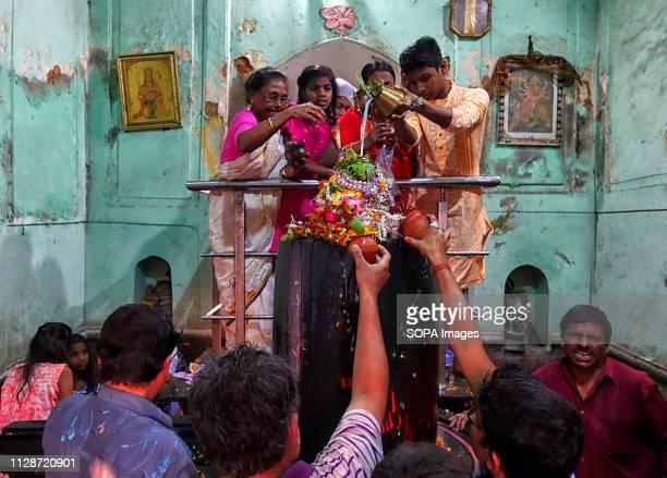 Hindu devotees seen pouring milk and water on the idol of Lord Shiva during Maha Shivaratri Festival inside Bhukailash Temple in Kolkata