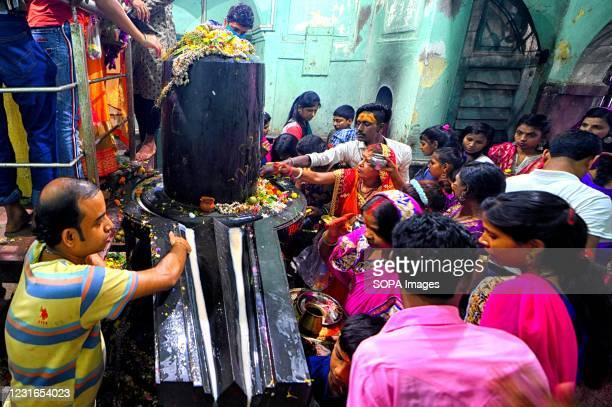 Hindu devotees seen pouring milk and water on the idol of Lord Shiva during Maha Shivaratri Festival inside a ShivaTemple at Kolkata.