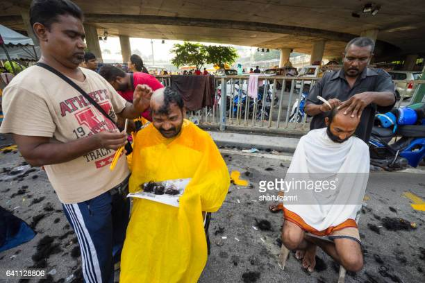 hindu devotees shaving  their head in a procession to the batu caves temple on thaipusam day - shaifulzamri stock pictures, royalty-free photos & images