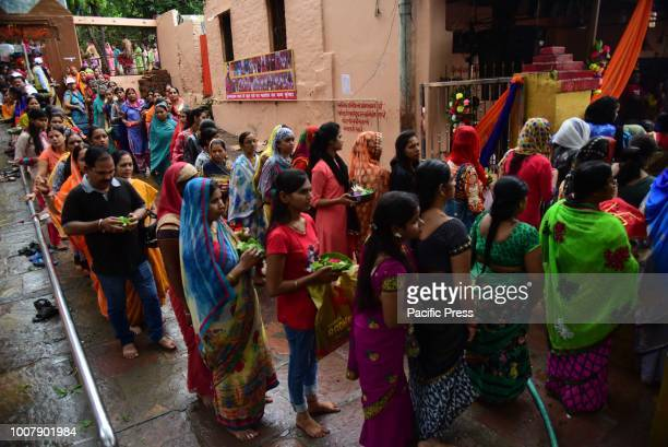 Hindu devotees stand in a queue to perform Abhishek to Lord Shiva as they offer prayer at historical Mankameshwar temple on the 1st monday of Shrawan...