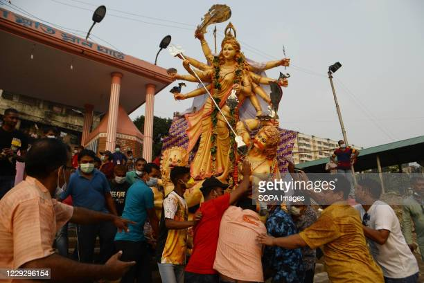 Hindu devotees submerge a clay idol of the Hindu goddess Durga in the River during the final day of the Durga Puja festival. Health officials have...